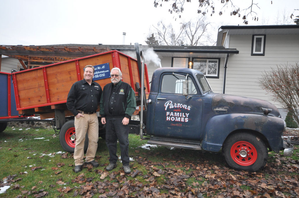 Taylor parsons and gavin parsons stand in front of the Parsons Family Homes old dumptruck with the company logo painted on it