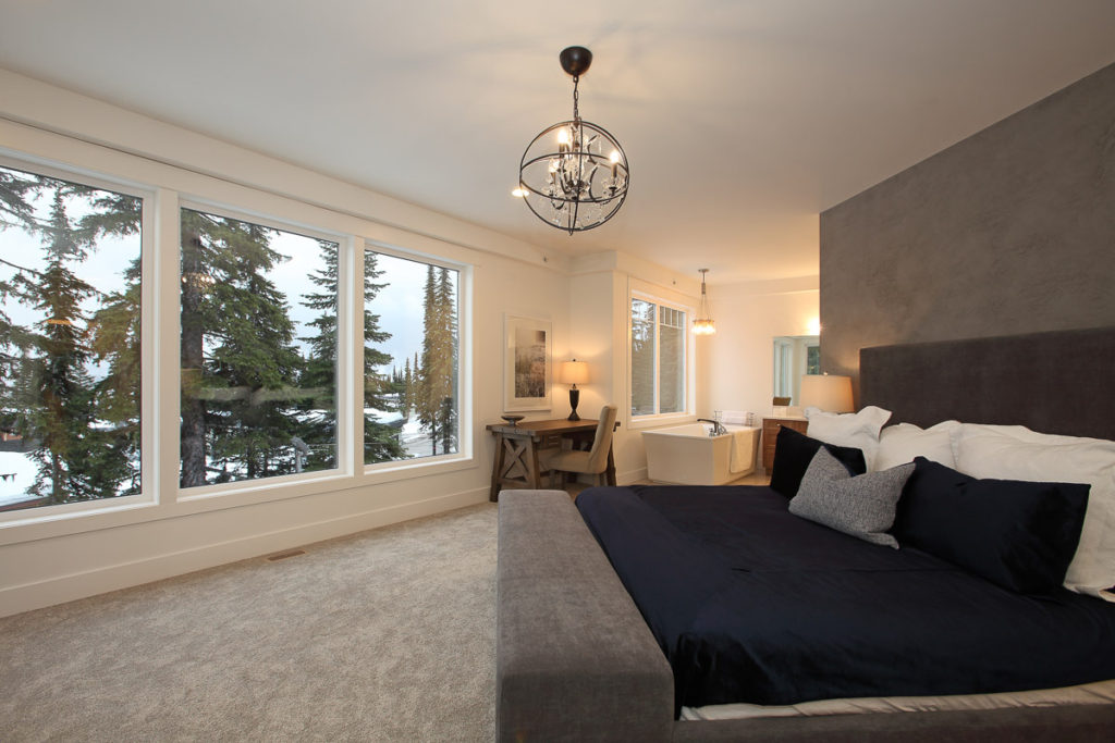 main bedroom with middle room wall and king bed overlooking mountains of silver star resort through large windows