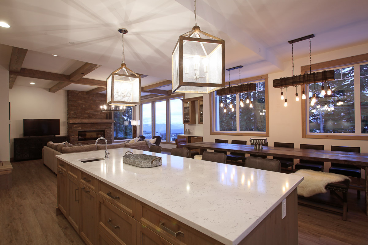 modern open concept kitchen with large lantern chandeliers lighting up a long island with a sink in it and a 16-person dining table up at silver star mountain resort community