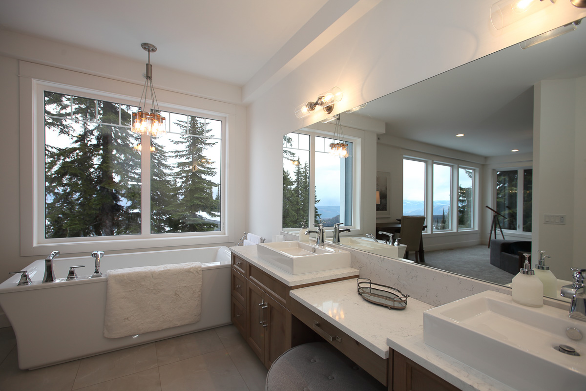 modern large bathroom with his and her white rectangular sinks, a stand alone with tub under large windows overlooking silver star resort in vernon, bc