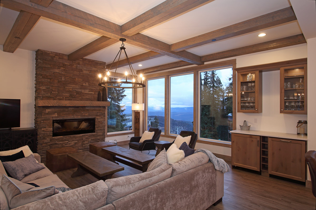 modern open concept beam and flat ceiling in a living room with floor to ceiling windows overlooking silver star mountain in vernon bc