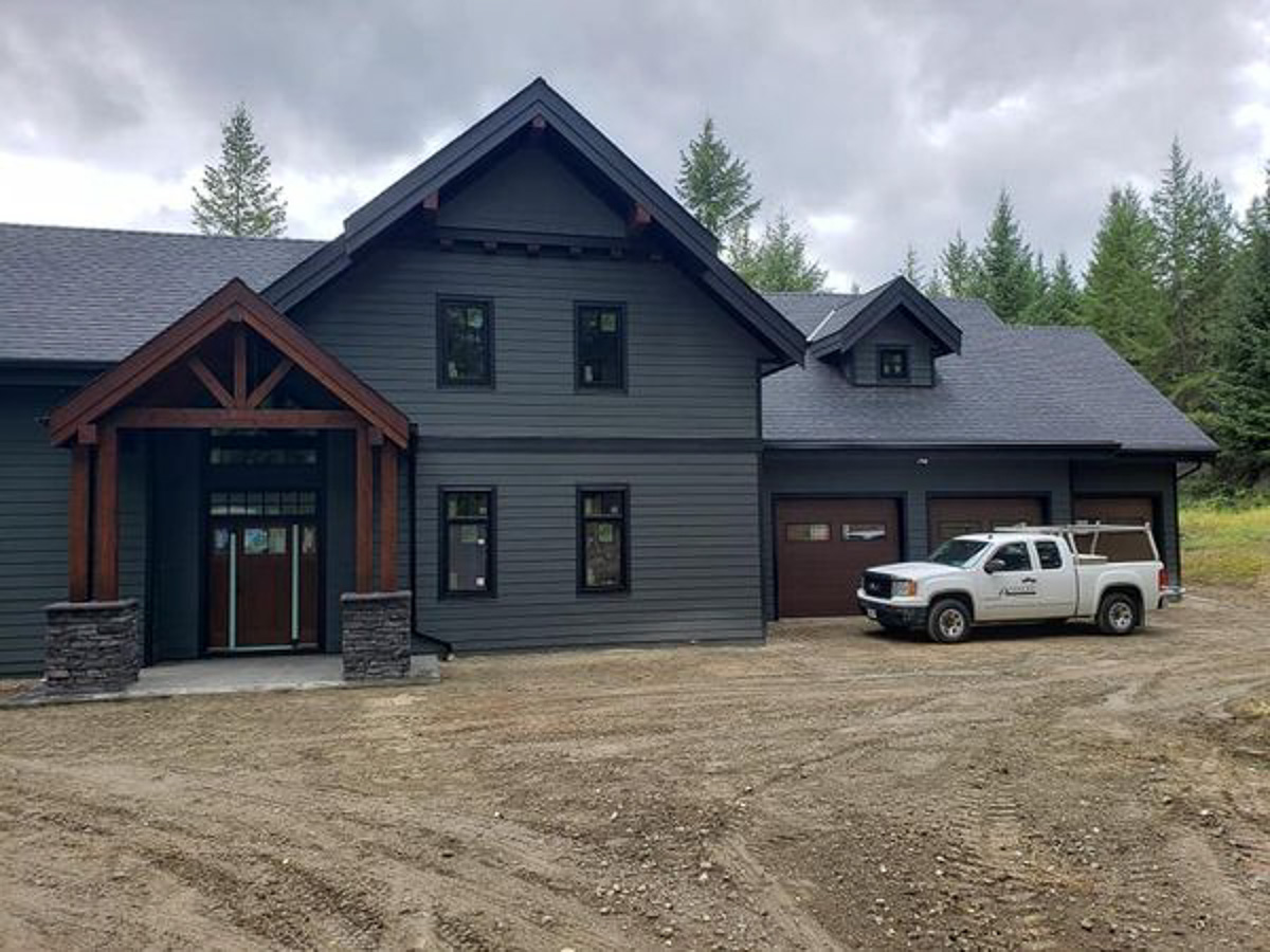 custom home built by parsons family homes showing blue-grey exterior with beam entrance and 3 car garage