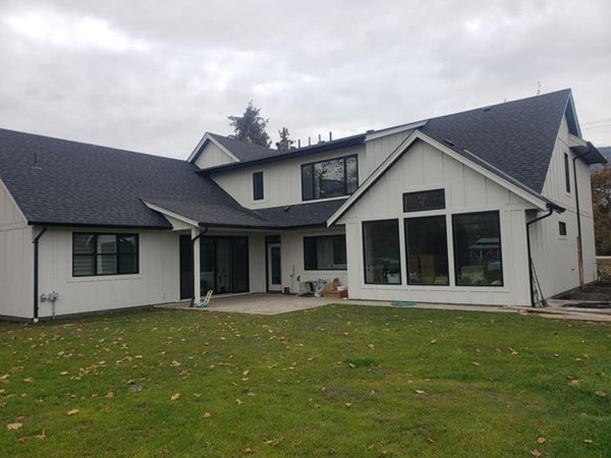 custom home build by parsons family homes with white wood paneling and dark wood outlining large windows set back at the end of a green lawn